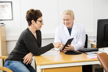 Patient And Male Doctor Communicating Over Digital Tablet