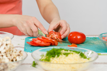 Close-up of female hands cutting tomato on kitchen table