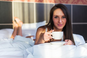 pretty woman on bed with cup of coffee portrait, looking at camera, front look