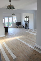 A Contemporary living area being decorated with white walls and floorboards ready to be painted