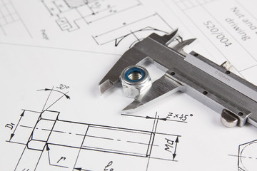 Caliper and nuts on a background of engineering drawings. Science, mechanics and mechanical engineering.