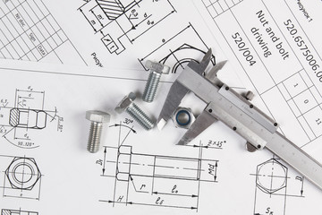 Caliper, bolts and nuts on a background of engineering drawings. Science, mechanics and mechanical engineering.