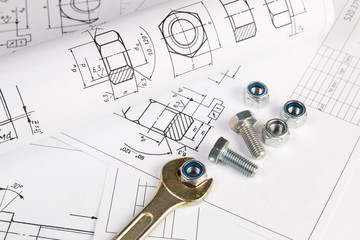 Wrench, bolts and nuts on a background of engineering drawings. Science, mechanics and mechanical engineering.