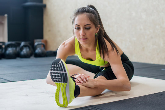 young woman stretching hamstring in gym, fit female doing warm-up on mat