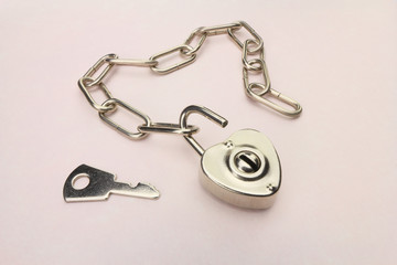 Heart shaped padlock and chain with key, unlocked, on a pink paper background