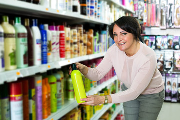 Elegant female customer buying conditioner for hair