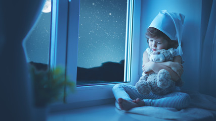 child little girl at window dreaming and admiring the starry sky