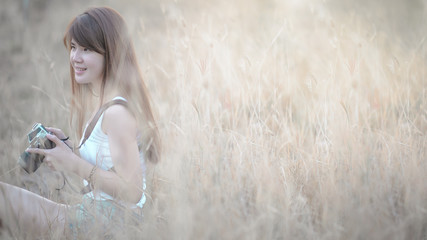 beautiful asian woman photographer holding camera seat in clump of grass with sunset time (selective focus)