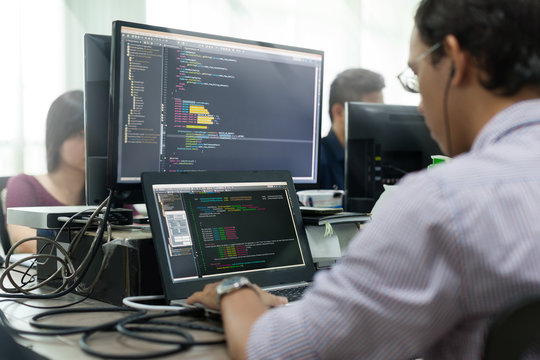 Asian Outsource Developer Looking Screen Sitting At Desk Working