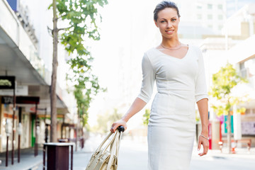 Business woman pulling suitcase bag walking in city