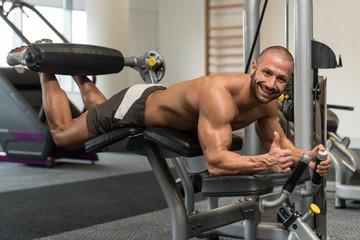 Bodybuilder Doing Lying Leg Curls Exercises On Machine