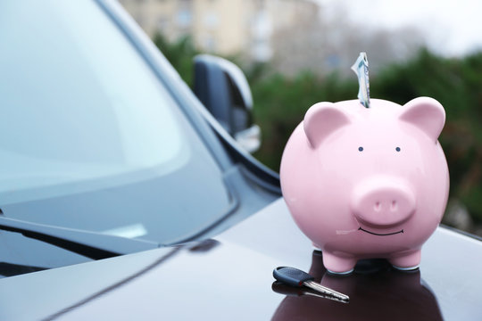 Piggy money box with cash and key on car bonnet at the street
