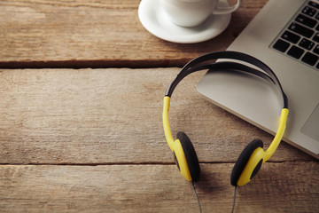 Laptop and earphones on wooden background