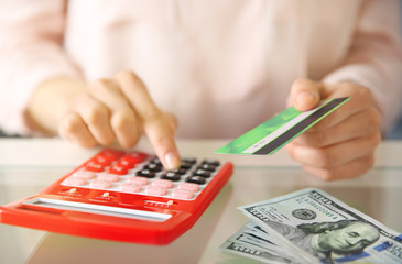 Female calculate with credit card and money, closeup