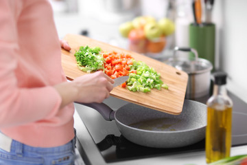 Woman frying vegetables in kitchen