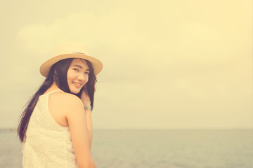 Outdoor summer portrait of young pretty woman looking to the ocean at tropical beach, enjoy her freedom and fresh air, wearing stylish hat and clothes, Vintage filtered image.