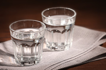 Glasses of water with napkin  on wooden background