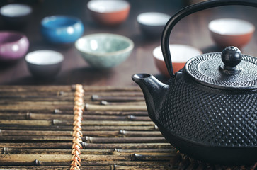 Traditional oriental teapot on bamboo placemat