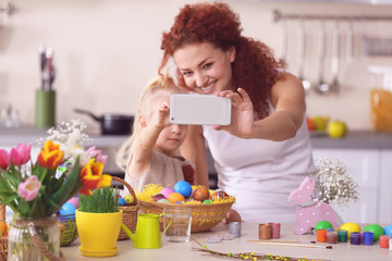 Mother and daughter making selfie while decorating Easter eggs in the kitchen