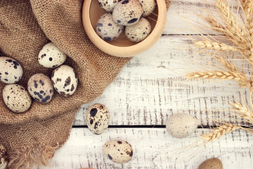 Quail eggs on rustic wooden background. Top view