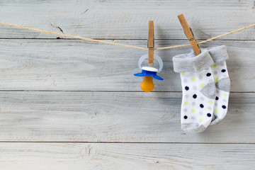 Baby pacifier and socks hanging on clothesline on wooden background