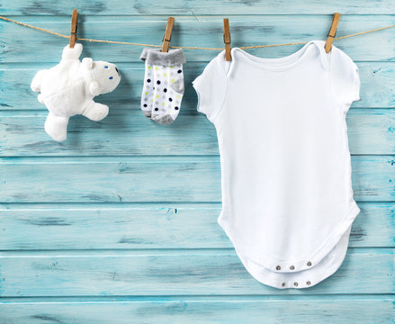 Baby boy clothes and white bear toy on a clothesline