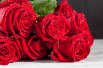 Bouquet of red roses with water dew drops on white wooden rustic table. Shallow depth of field.