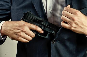 man in suit holding gun