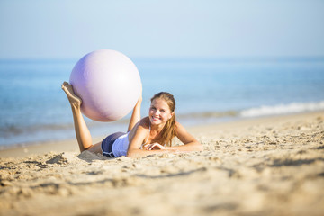 .Healthy woman with  exercise ball at the beach