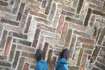 Male feet stand on old cobblestone pavement