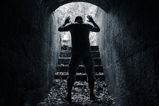 Man leaves dark stone tunnel with raised hands