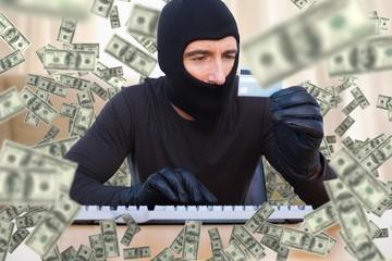 Composite image of burglar with balaclava hacking a laptop