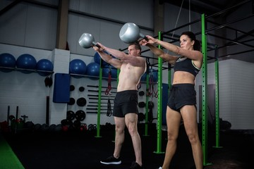 Man and woman exercising with kettlebell