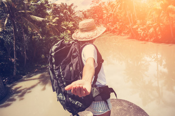 Traveling woman with backpack and straw hat walking near tropical river (intentional sun glare)