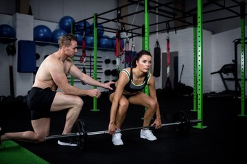 Trainer instructing a woman while lifting barbell