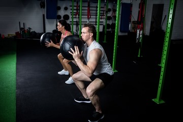 Man and a woman exercising with a medicine ball