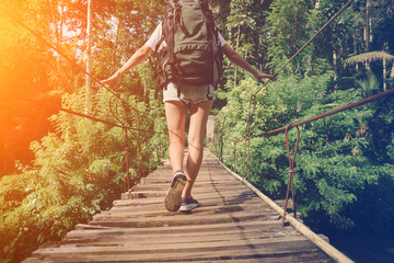 Young woman with backpack balancing across hanging bridge in tropical forest (intentional sun glare)