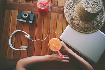Freelance woman and the table with fresh juice, laptop, film camera, mobile phone and headphones (intentional vintage color)