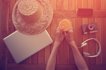 Woman sitting at the table with fresh juice, laptop, film camera, mobile phone and headphones (intentional vintage color and sun glare)