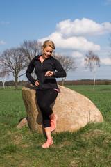 Joggerin lehnt an einem Findling und schaut auf ihren Fitness Tracker