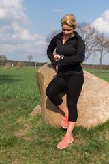 Blonde Joggerin schaut nach dem Sport auf den Fitness Tracker