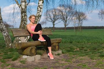 Joggerin sitzt nach Lauf auf der Bank im Freien und macht Pause