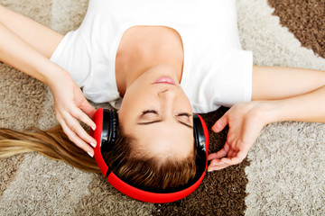 Young woman lying on the carpet and listenig a music in headphones