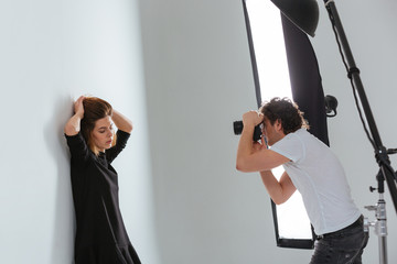 Man photographing female model in professional studio