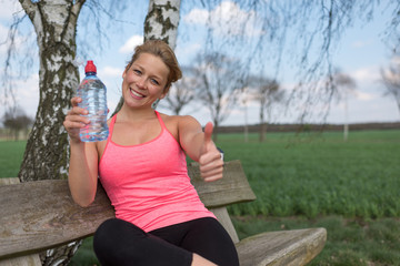 Joggerin sitzt draussen auf der Bank mit einer Wasserflasche und zeigt Daumen hoch