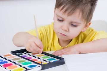 kleinkind malt mit bunten wasserfarben