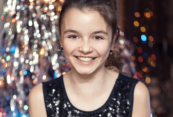 Young beautiful girl smiling and holding a Christmas tree. In black dress happy.