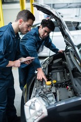 Mechanics examining car engine using digital tablet
