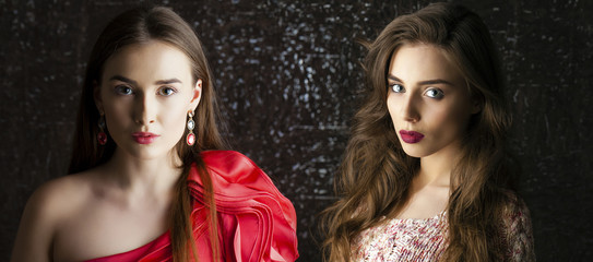 Two Young brunette women on dark studio wall background