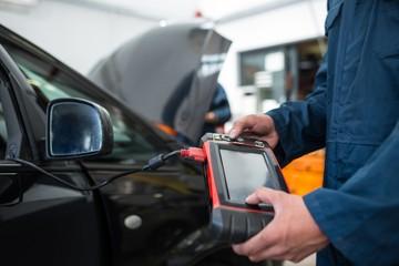 Mechanic using a diagnostic tool at the repair garage